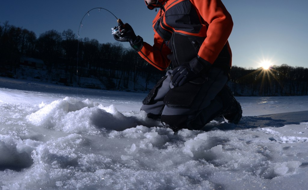 Ice fishing on a lake in winter