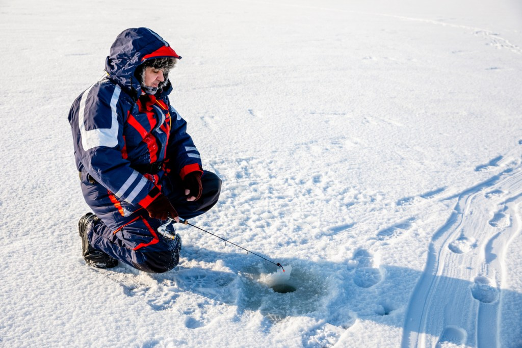 A fisherman is fishing with a winter