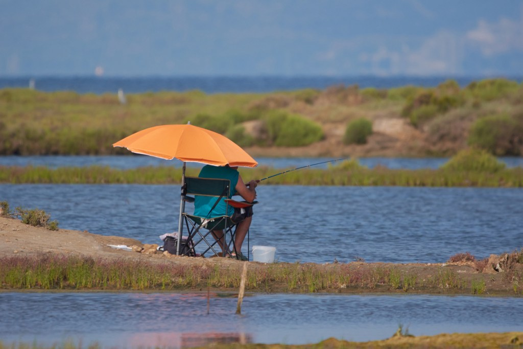 Tourist fishing with his rod under an orange umbrella
