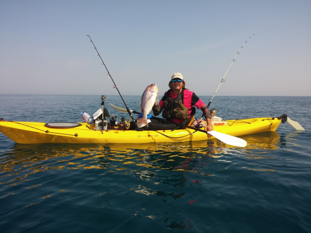 Man holds a large fish that he has caught from a kayak